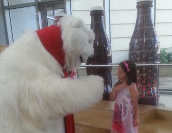 The Coca-Cola Bear at the World of Coca-Cola saying hello to a girl